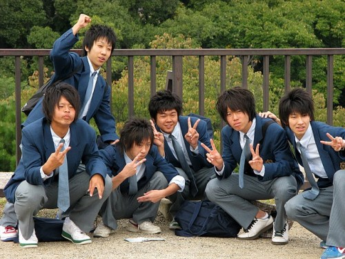 Six boys in school uniforms, and with matching hairstyles pose for a photo